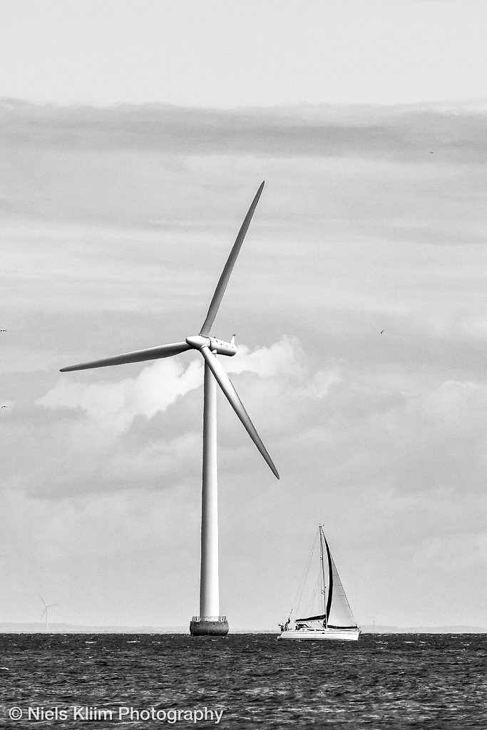 Three wind mills standing offshore at sea